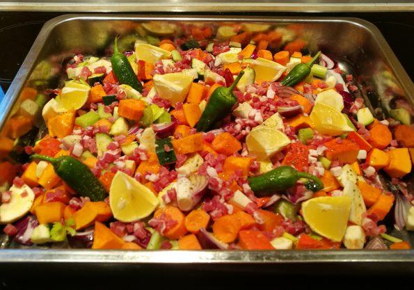 Gemüse und Speck in der Pfanne - fertig für den Ofen